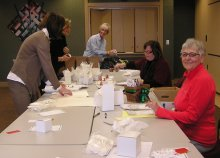 Hospice community volunteers help stuff bags